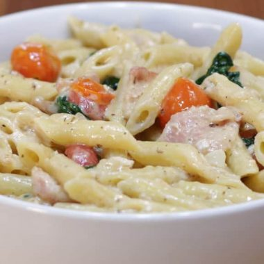 white bowl with bacon, tomatoes, spinach, white sauce, and penne noodles
