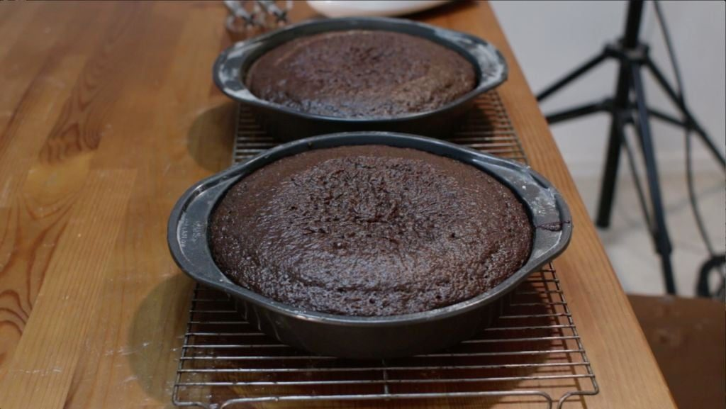 Freshly baked chocolate cake in cake pans on wire racks