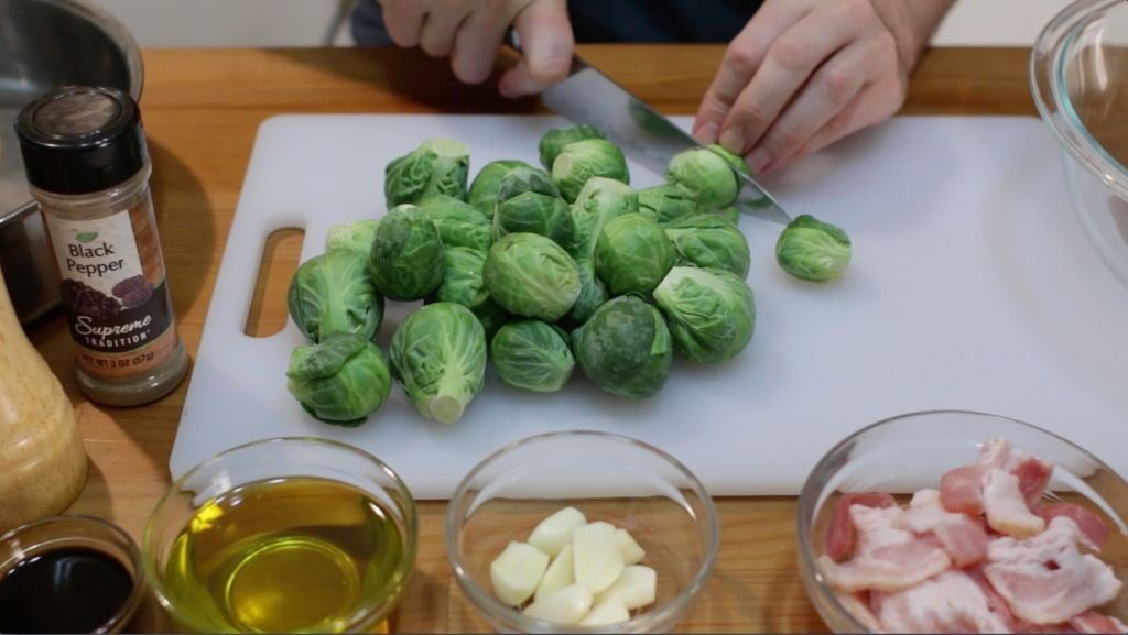 Hand cutting Brussels Sprouts with a knife on a white cutting board.
