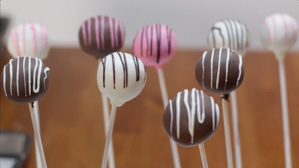 Several homemade cake pops drizzled with white and dark chocolate.