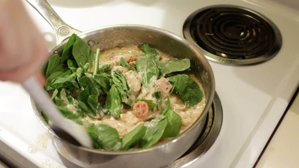 chicken and spinach being stirred into white pasta sauce