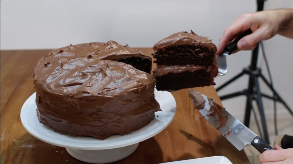 Large homemade chocolate cake on white cake stand and man holding a slice with metal cake spatula.