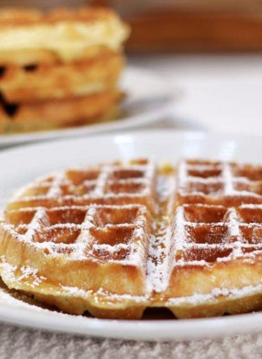 restaurant style belgian waffles on a white plate with powdered sugar