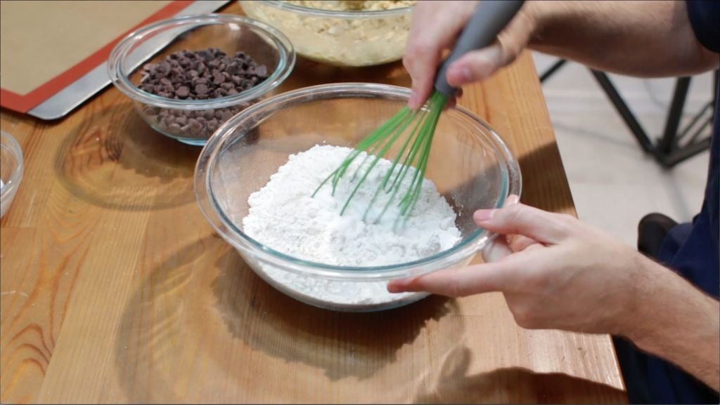 Hand holding green whisk mixing flour and other dry ingredients.