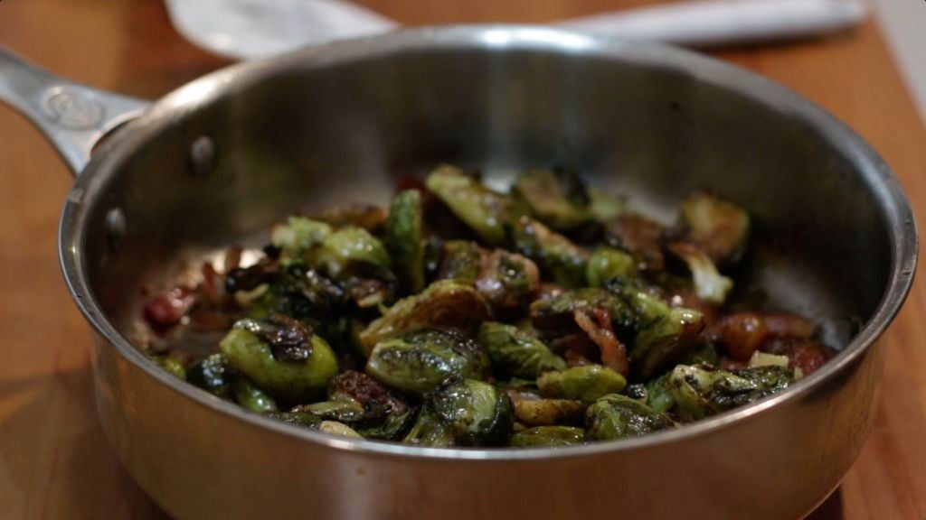 Stainless steel skillet on a wooden table holding roasted Brussels sprouts with bacon.