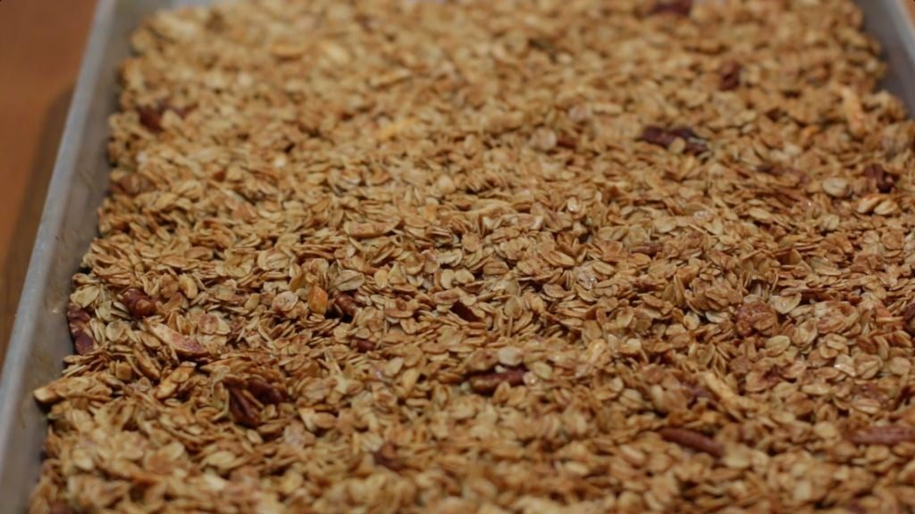 Homemade granola sitting flat in a sheet pan on a wooden table.
