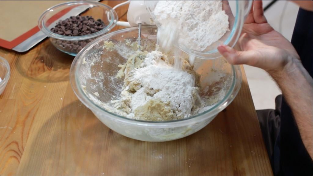 Hand pouring flour into a large glass bowl of chewy chocolate chip cookie dough.
