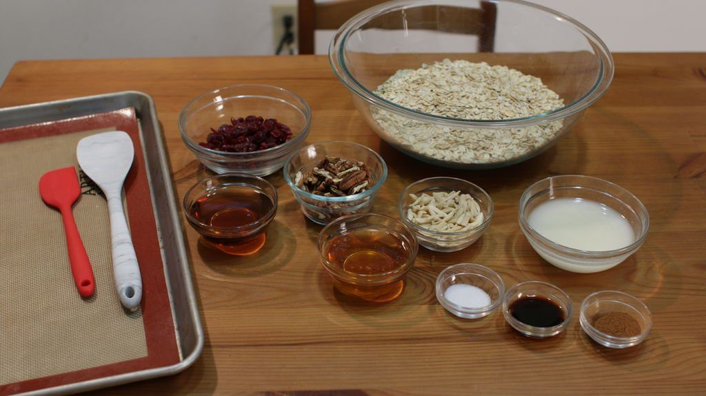 variety of homemade granola ingredients in glass bowls sitting on wooden table.
