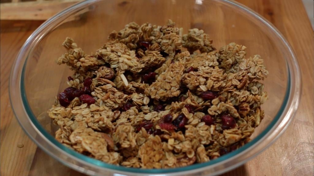 Broken up homemade granola with craisins in a large glass bowl on a wooden table.