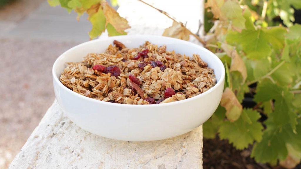 Homemade granola with craisins in a large white bowl outside on a wall.
