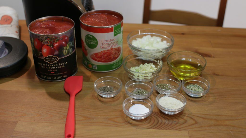 various pizza sauce ingredients in cans and glass bowls on top of wooden table