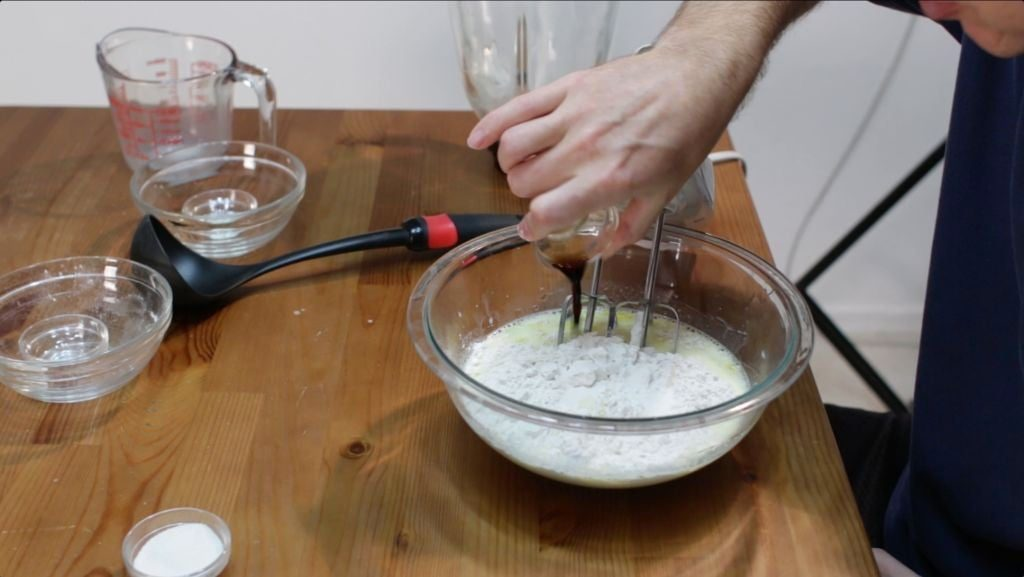 Man pouring vanilla extract into a large glass bowl with flour and other ingredients for crepes.