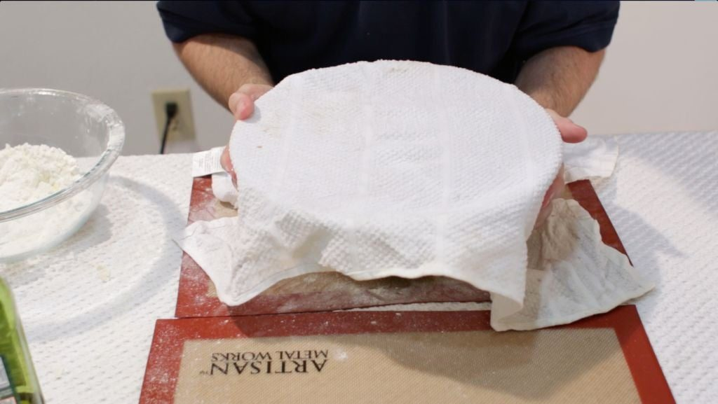 Man holding bowl of rising pizza dough that is covered with a white cloth.