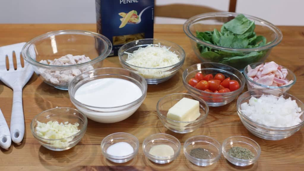 Several glass bowls holding white pasta sauce ingredients on top of a wooden table.