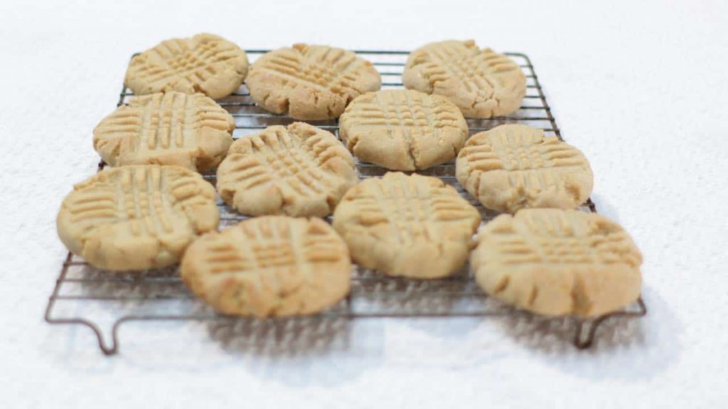 A batch of peanut butter cookies on a wire rack on top of white table cloth.