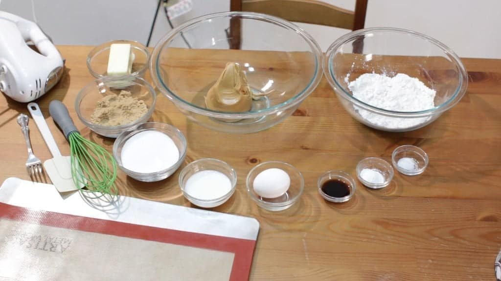 Several glass bowls on wooden table containing peanut butter, flour, sugar, etc. for making cookies.