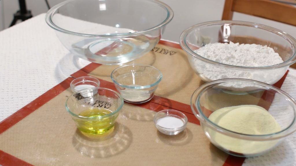 Bowls of different pizza dough ingredients sitting on a table.