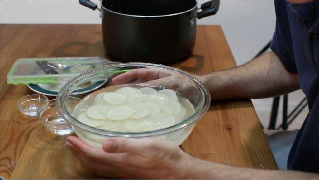 Thin slices of potato sitting in glass bowl of water on a wooden table.