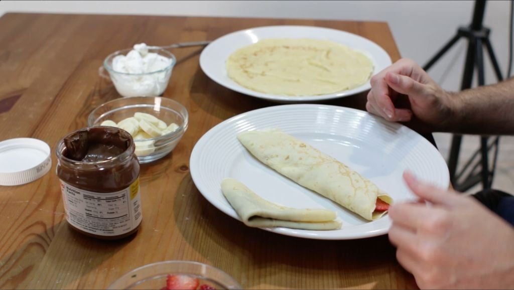 Homemade rolled crepe sitting on top of a white plate.