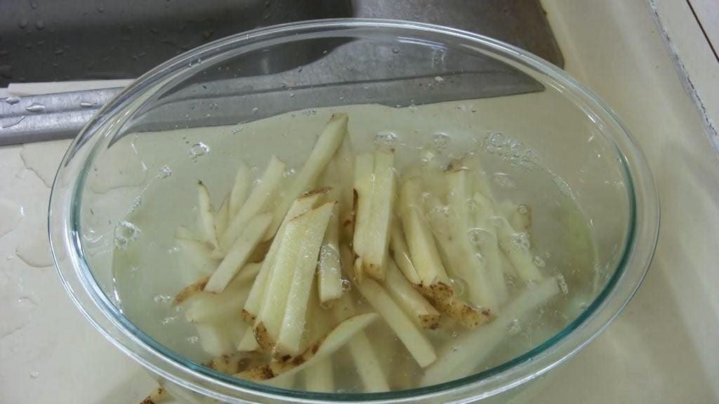 Glass bowl full of water and soaking french fries.