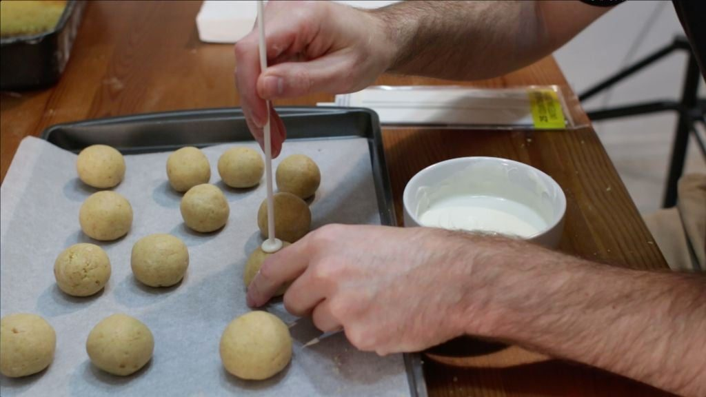 Sticking homemade cake pop ball with white stick and white chocolate.