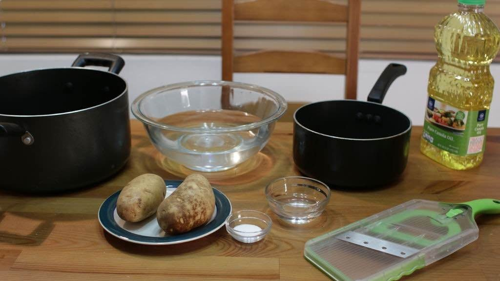 Group of tools and ingredients for making thin crispy potato chips.