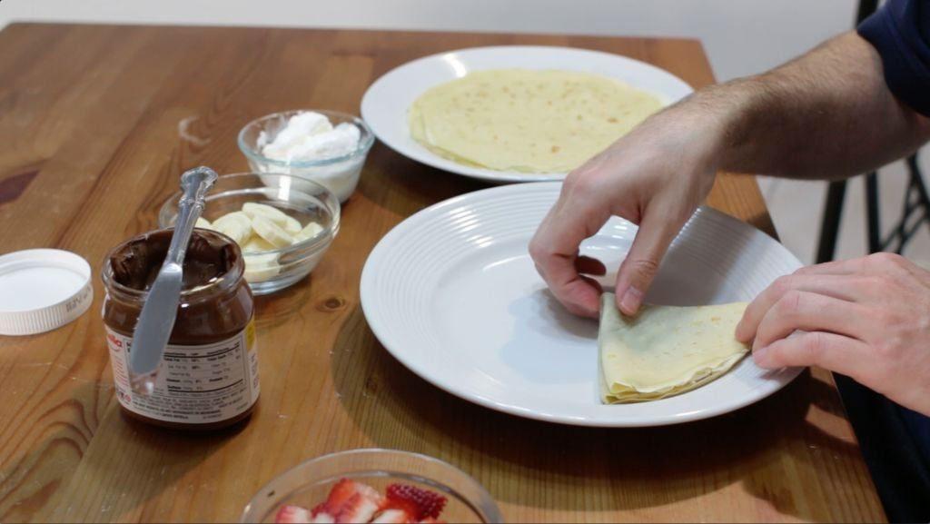 Hand folding crepes into a triangle shape on a white plate.
