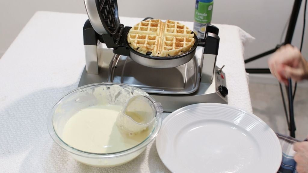homemade Belgian waffles cooking on a waffle iron on a table.