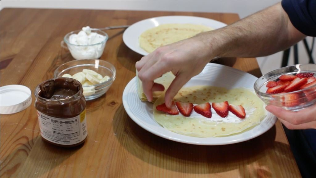 Hand placing cut strawberries crepes with whipped cream.