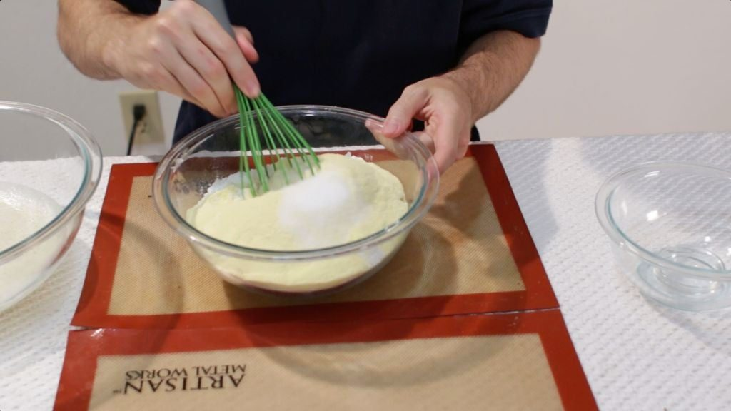 Hand with green whisk mixing flour and semolina.