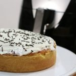 Yellow air fryer cake topped with frosting and sprinkles.