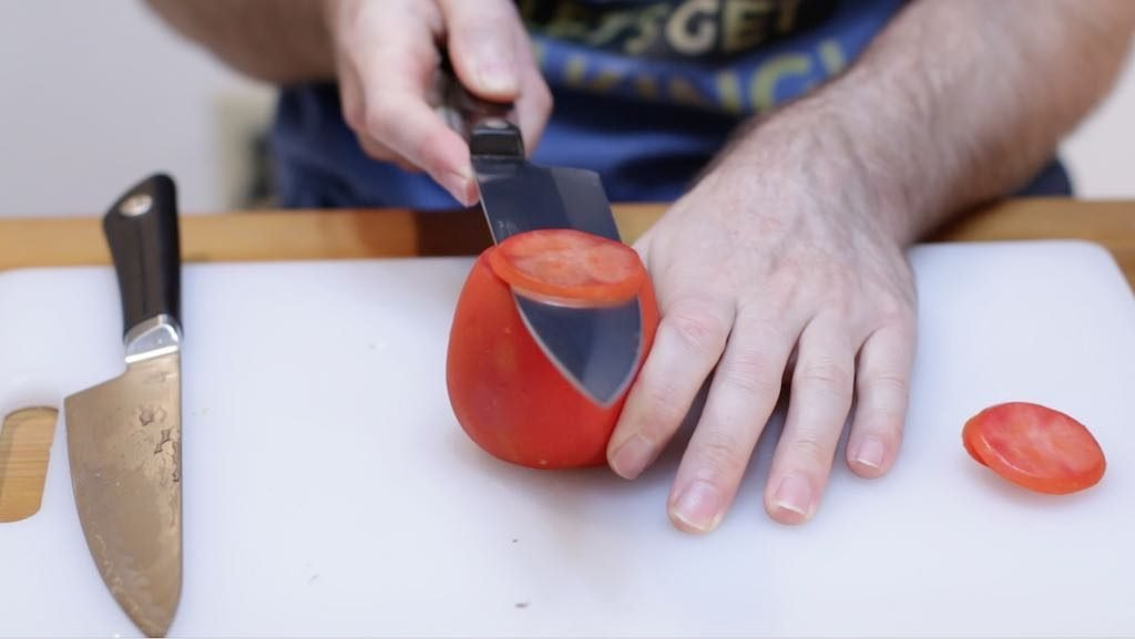 Hand holding a Cutco chef knife thinly slicing a tomato.