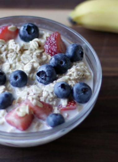 glass bowl full of overnight oats with strawberries and blueberries