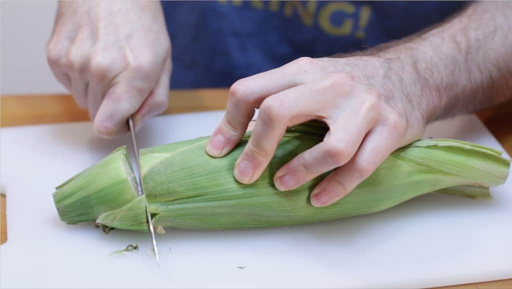 Hand holding a knife cutting through an ear of corn in its husk.