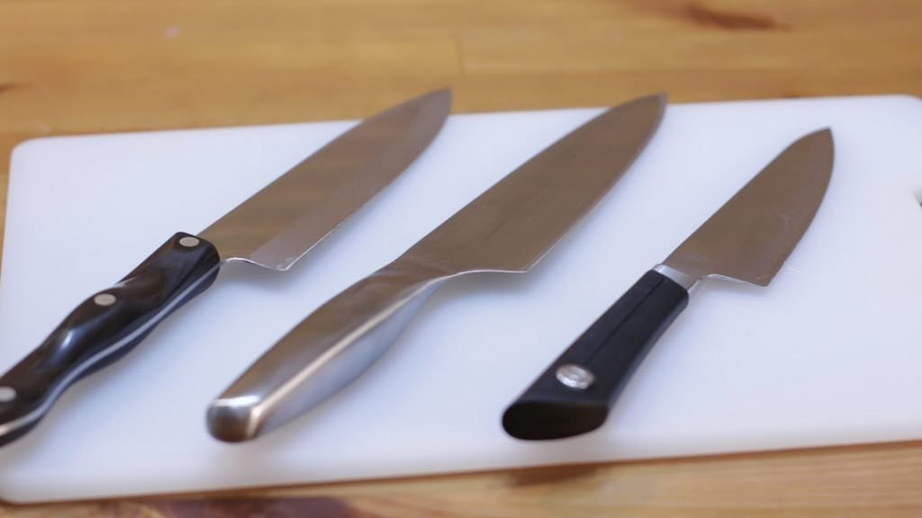 Three chef knifes lying on a white cutting board on wooden table.
