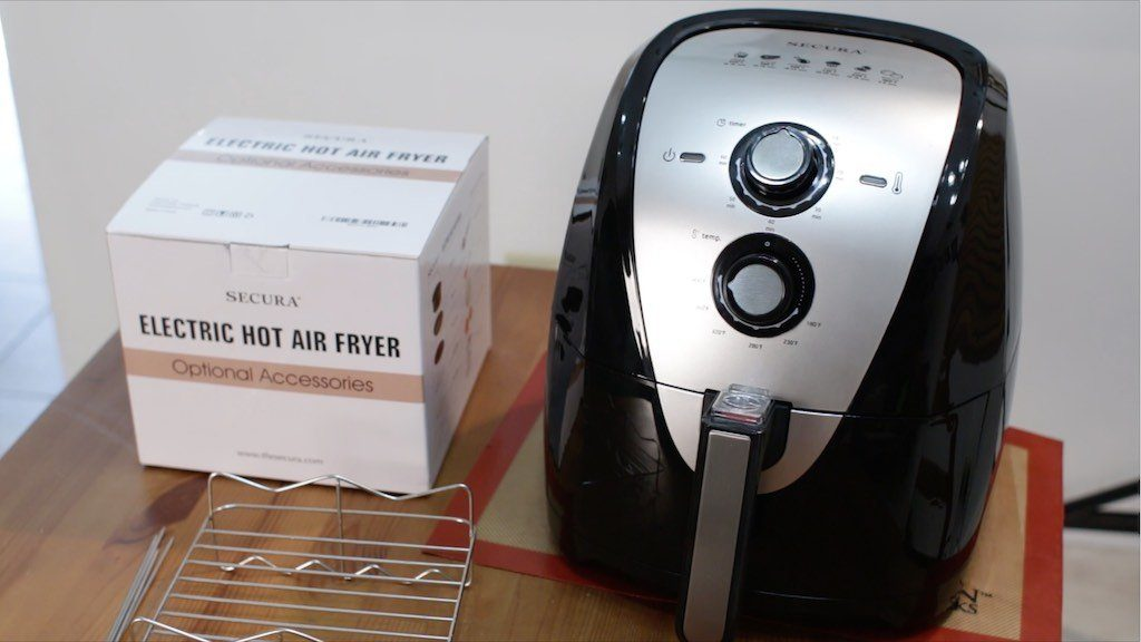 Secura Air Fryer sitting on a wooden table next to a box of air fryer accessories.