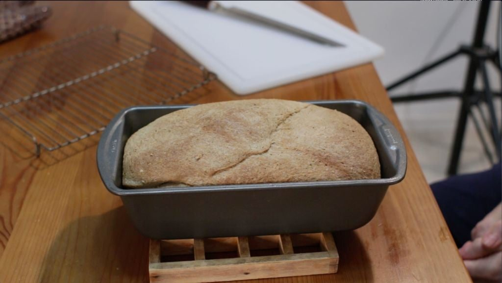 Finished acorn bread loaf in pan on top of wooden table.