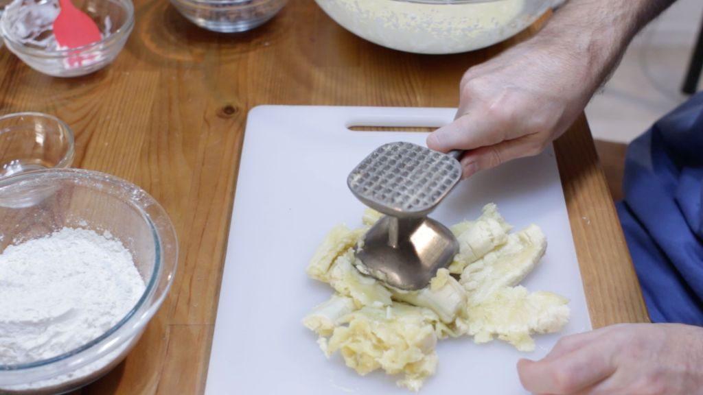 hand holding a meat tenderizer mashing bananas