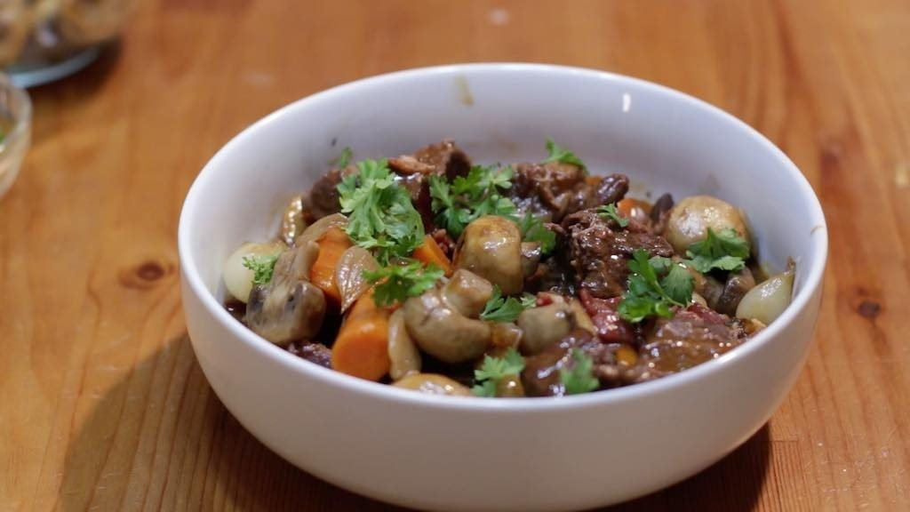 White bowl holding freshly made beef bourguignon sitting on a wooden table.