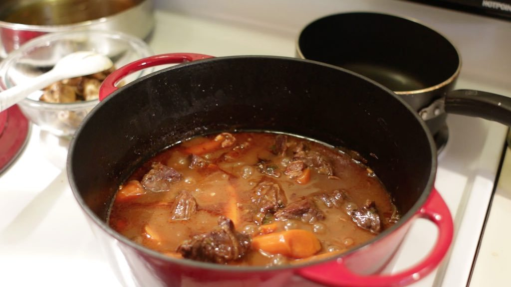 Beef bourguignon braising in a red enameled dutch oven.