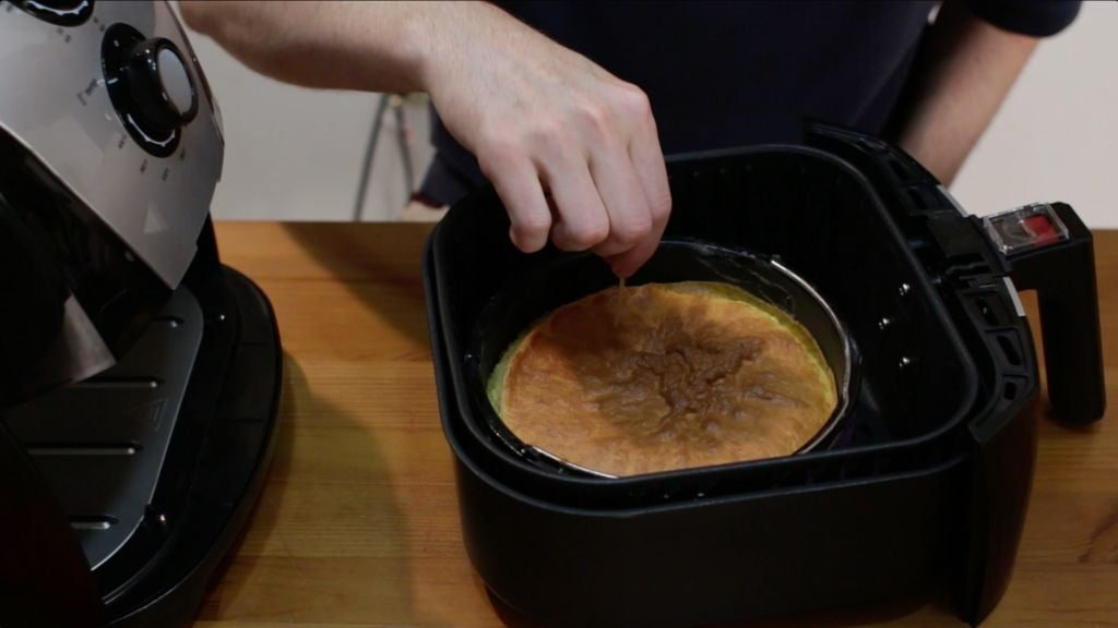 hand with toothpick poking the middle of a cake sitting in an air fryer basket.
