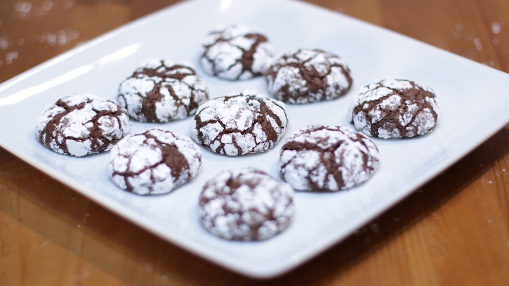chocolate crinkles cookies on white plate on top of wooden table