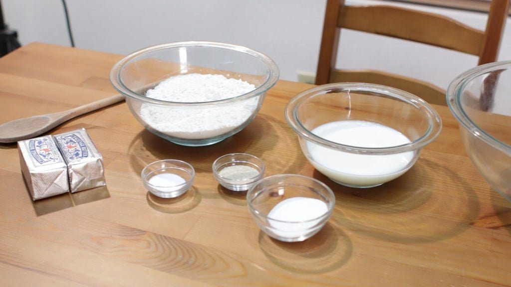 Flour, milk, and other ingredients in glass bowls on a wooden table.