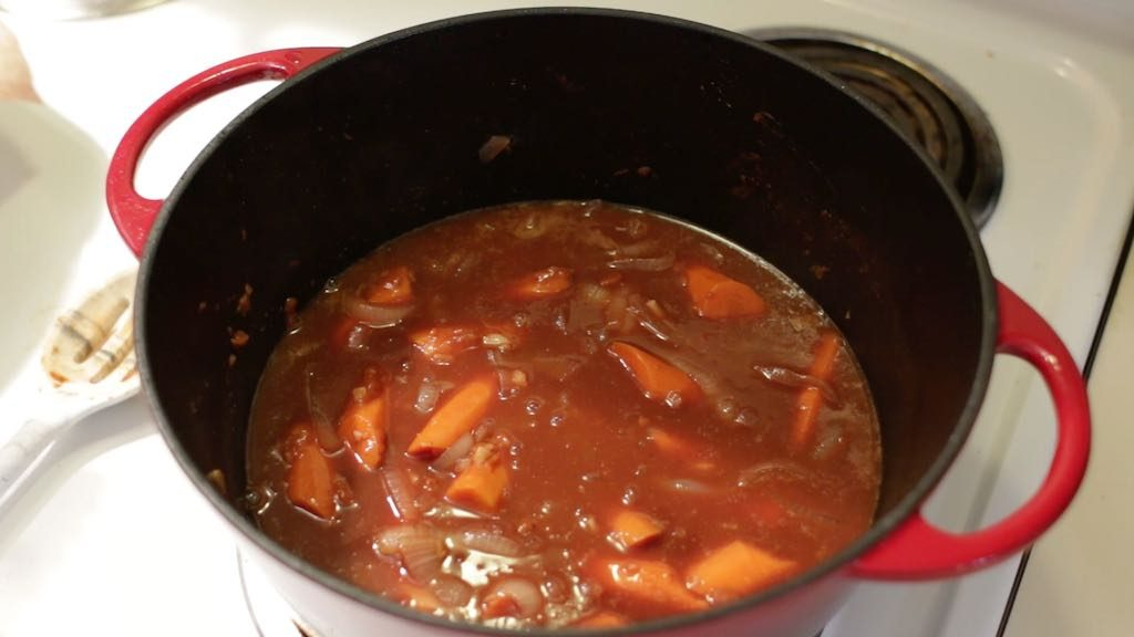 Beef bourguignon in a red dutch oven with red wine.