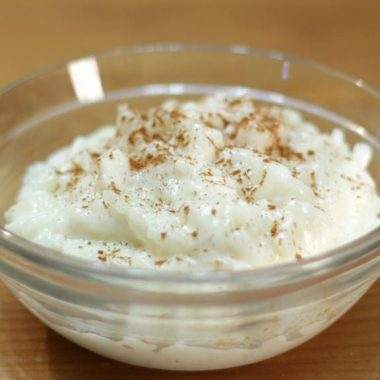 Glass bowl of rice pudding topped with cinnamon
