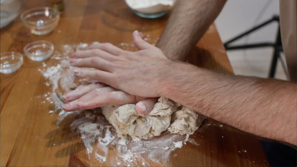 Two hands kneading dough on a floured brown wooden table.