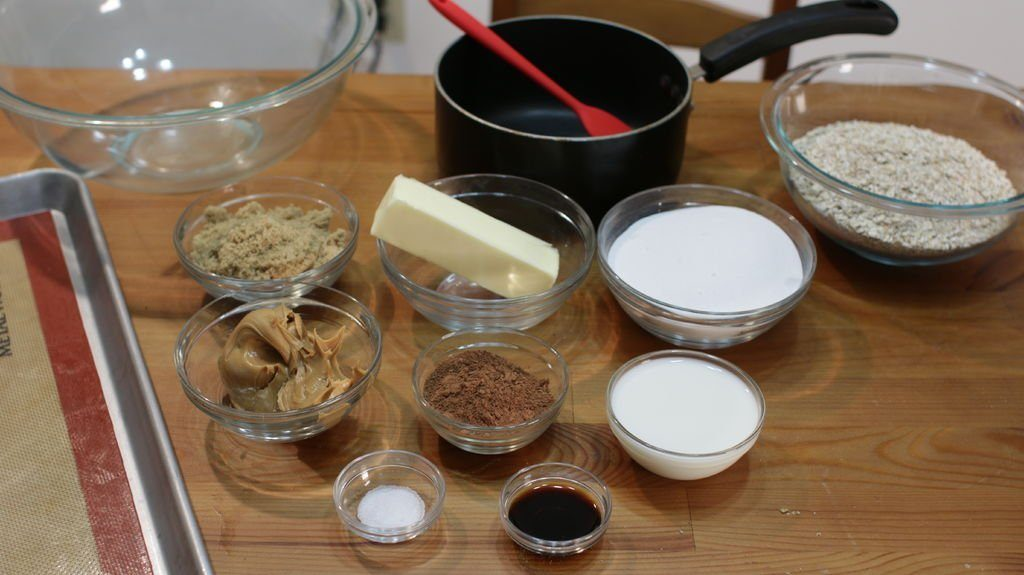 Several glass bowls holding ingredients to make no-bake chocolate oatmeal cookies.