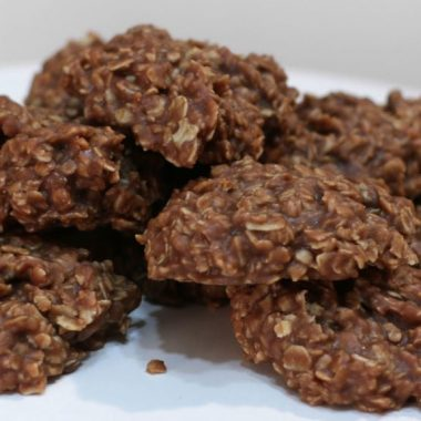several no-bake chocolate oatmeal cookies piled on a white pedestal