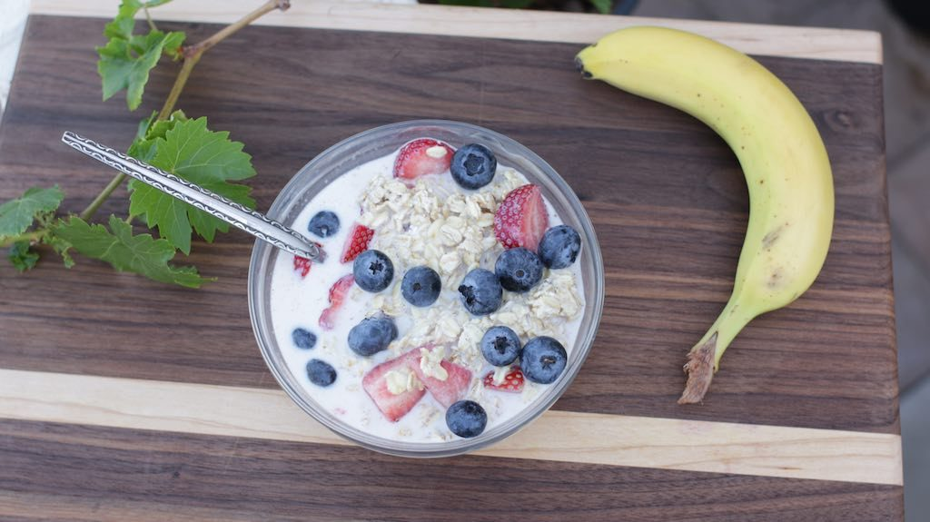 overnight oats on a glass bowl outside with a banana on a dark brown wooden cutting board.