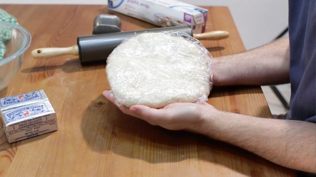 Two hands holding croissant dough wrapped in plastic wrap.